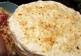 coating frosted cake with toasted coconut