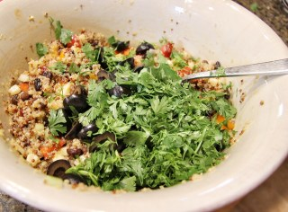 tossing quinoa salad