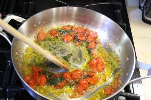stirring tomatoes and herbs