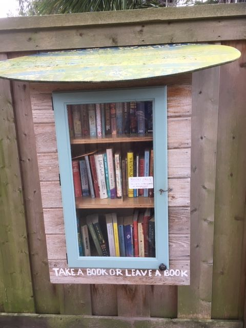 A Free Little Library that is built into a fence.