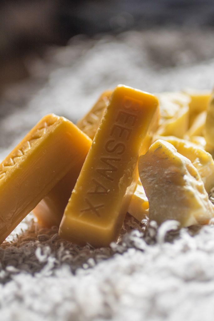 Close up photograph of solid yellow beeswax in rectangular block form, as well as pieces of wax.