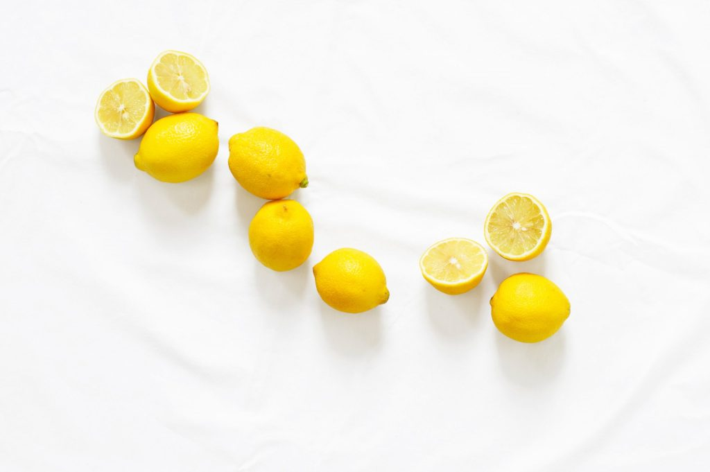 Whole and cut lemons in random a pattern on a white cloth to illustrate that in an essential oil blend, lemon would be a top note.