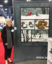 Barbara with the Solstice BOM quilt in Aurifil's booth at Houston Quilt Market 2017