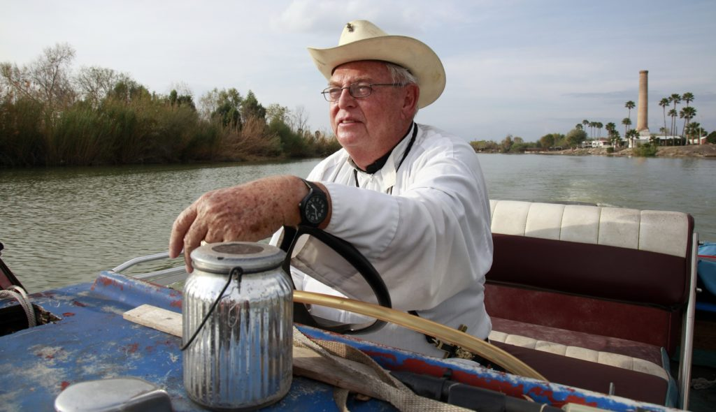 In this Tuesday, Jan. 8, 2019 photo, father Roy Snipes, pastor of the La Lomita Chapel, shows Associated Press journalists the land on either side of the Rio Grande at the US-Mexico border in Mission, Texas. Portions of Father Snipes' church land in Mission could be seized by the federal government to construct additional border wall and fence lines. Rather than surrender their land to the federal government, some property owners on the Texas border are digging in to fight President Donald Trump's border wall. They are rejecting buyout offers and preparing to battle the administration in court. Trump is scheduled to travel to the border Thursday to make the case for his $5.7 billion wall. (AP Photo/John L. Mone)