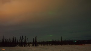 Light pollution bouncing off a cloudy sky with minimal aurora.