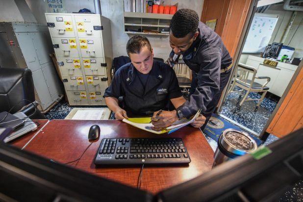 Yeoman 1st Class Gregory Nicolaisen, left, and Chief Yeoman Nick Smith review a request paperwork aboard the aircraft carrier USS Theodore Roosevelt (CVN 71).