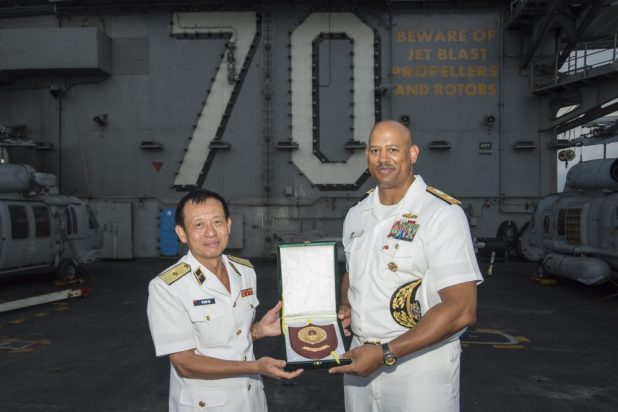 Rear Adm. John Fuller (right), commander of Carl Vinson Strike Group, accepts a plaque from Vietnamese Rear Adm. Do Quoc Viet, commander, Navy Region 3 while aboard USS Carl Vinson (CVN 70), March 6, 2018.
