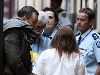 Shane Bond - accused of murdering the young barmaid - is escorted into the courthouse.