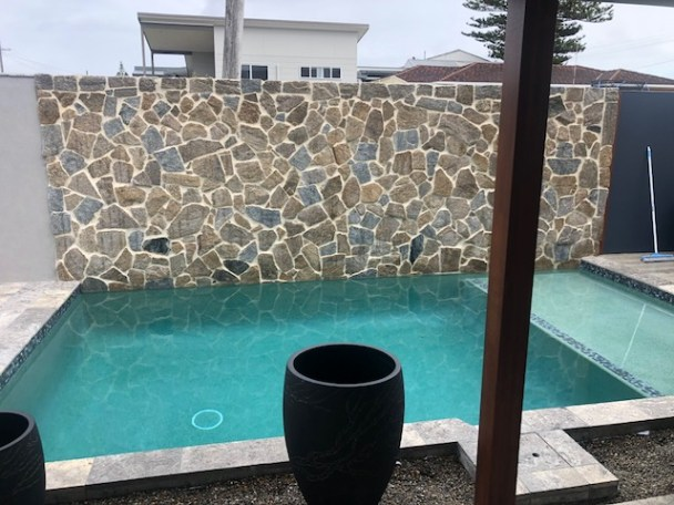 natural stone featured wall seen as swimming pool private wall with limestone tiles in flooring