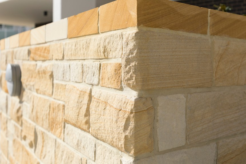 sandstone wall cladding wall with stone corners and matching capping stone