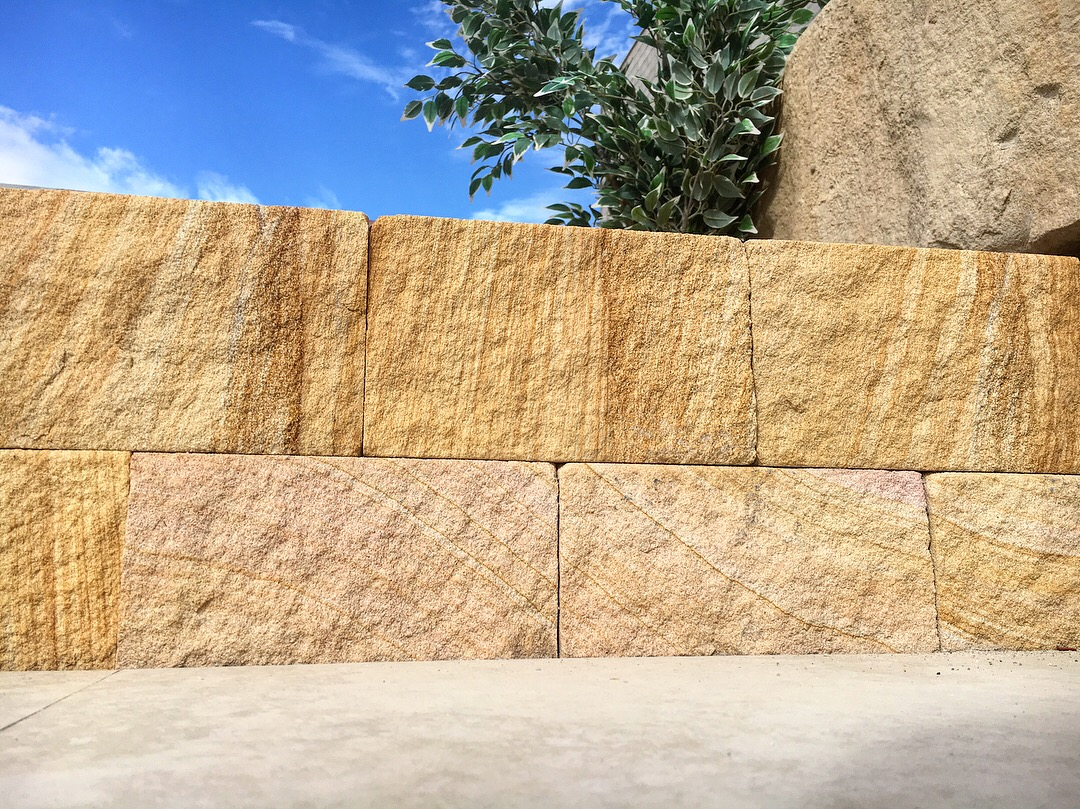 Retaining wall project using banded sandstone bricks, split stone block