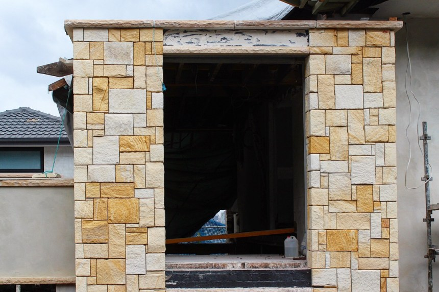 sandstone house under construction, the walling stone is banded colour, rectangular and square shape stone