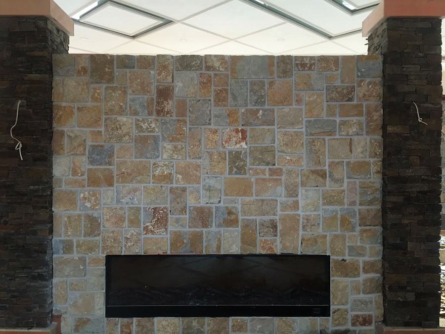 Stone fire place using Laverton irregular Limestone cladding and stone pillar seen in a house