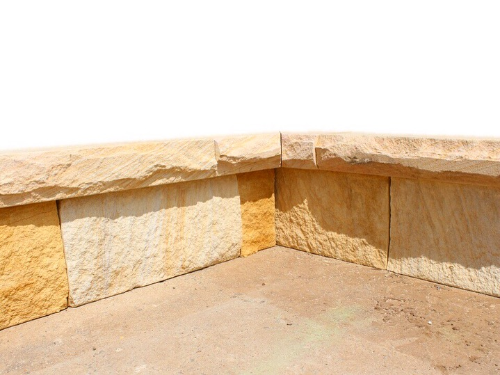 Garden edge design using banded sandstone bricks and capping stones, bricks are split surface and caps with rockface sides