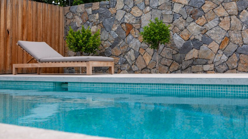 Swimming pool tiling with Tahiti glass mosaic pool tile and natural stone wall claddings