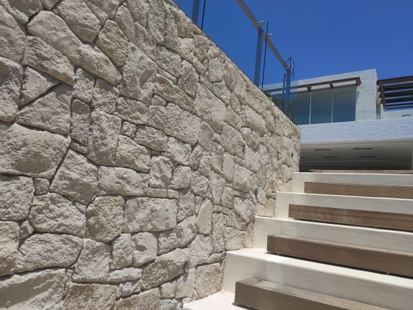 white irregular walling stone seen in a house wall with some marble stairs