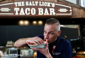 man eats taco from The Salt Lick's taco bar at Austin-Bergstrom International Airport