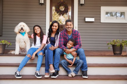 Family With Children And Pet Dog Sit On Steps Of Home