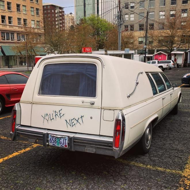 White Hearse with the words You're Next scrawled on the rear