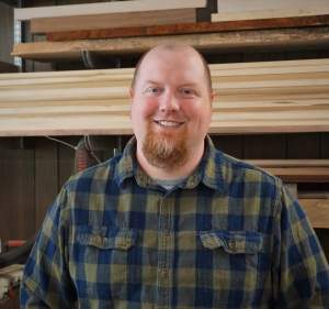 woodworking cnc instructor neil griffith in front of stack of wood
