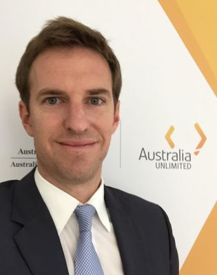 "Profile photo of Nicolas Bentel, Head of the new Austrade office in Zurich. Nicolas is pictured standing before an ""Australia Unlimted"" poster"