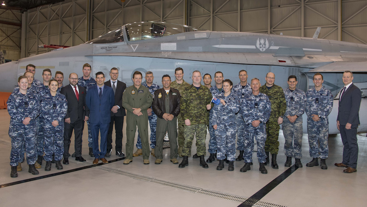 Members of the Royal Australian Air Force (RAAF), the Royal Canadian Air Force and representatives of the Interim Fighter Capability Project stand in front of the newly arrived RAAF F/A-18. (Cold Lake Imagery/Canada)