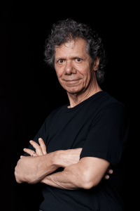 Chick Corea standing arms folded black background, smiling