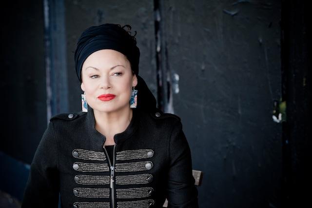 Tina Harrod publicity shot, headscarf, red lipstick,dark background.