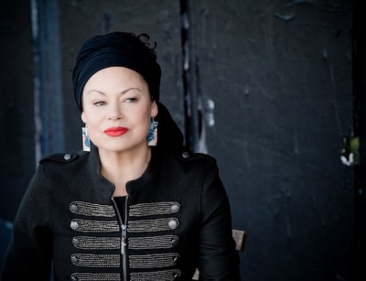 Tina Harrod publicity shot, headscarf, red lipstick,dark background.