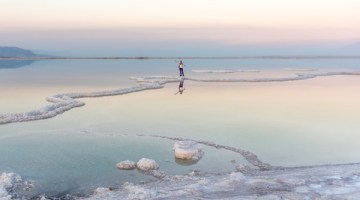 Women standing in the Dead Sea at Sunset