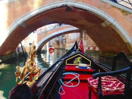 A gondola quietly glides through a small canal.