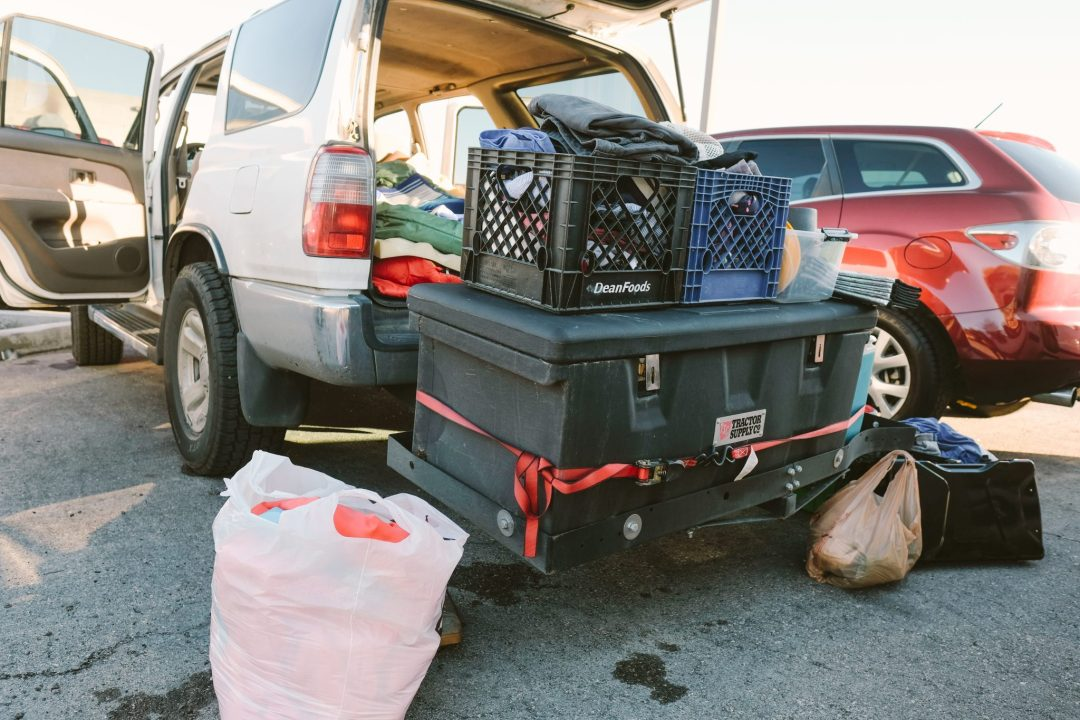 A Toyota 4Runner loaded up with travel gear and a hitch with a box.