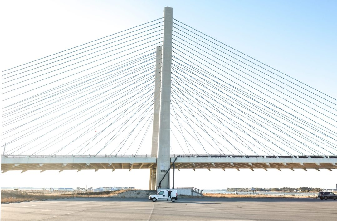 Erin McGrady jumping in front of the Indian River Inlet Bridge in Delaware and Ram Promaster City van.