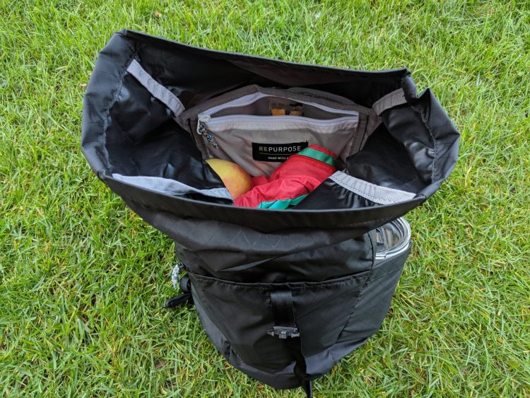 CamelBak Pivot Roll Top Backpack open with a red vest and apple inside.