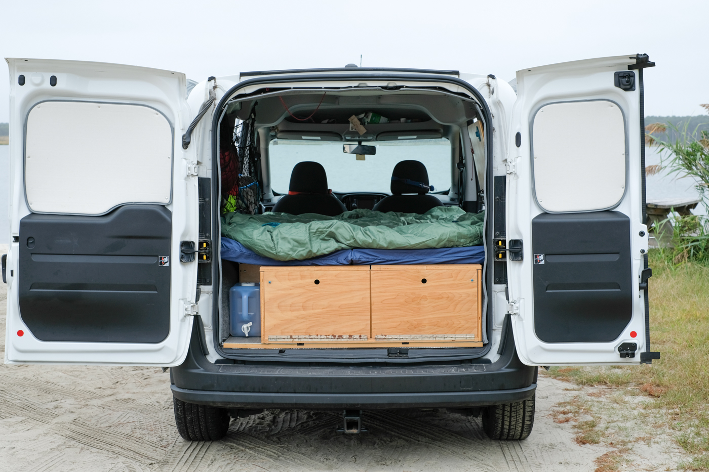 back of a ram promaster city van with a DIY van life bed