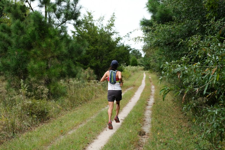 Erin McGrady running on a trail in Delaware in the Women's Hoka One One Challenger ATR 5's