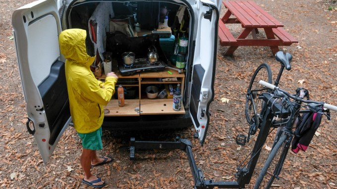 a woman making coffee in a yellow rain coat outside the back of a camper van.