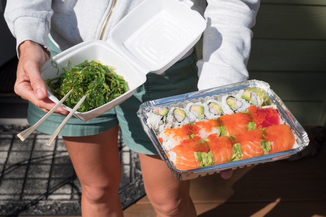 A woman holding sushi and seaweed salad from Soba Sushi and Noodle House in Weaverville, NC.