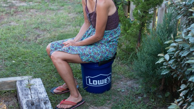 woman sitting on a DIY camper van toilet.