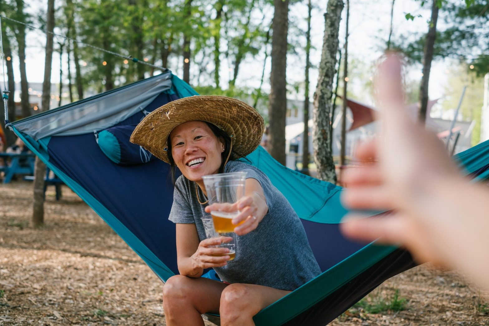 Erin McGrady sitting in ENO's SkyLoft Hammock in the meadow area at Highland Brewing in Asheville, NC. She is wearing a straw hat and is holding a cup with beer in it and offering one to a blurred out hand in the foreground.