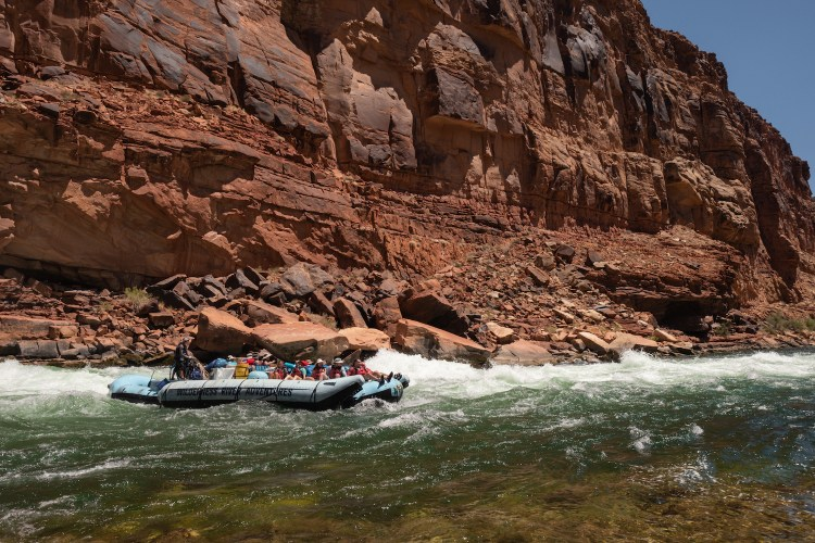 Wilderness River Adventures' blue raft runs the rapids in the Colorado River in the Grand Canyon on a sunny day.