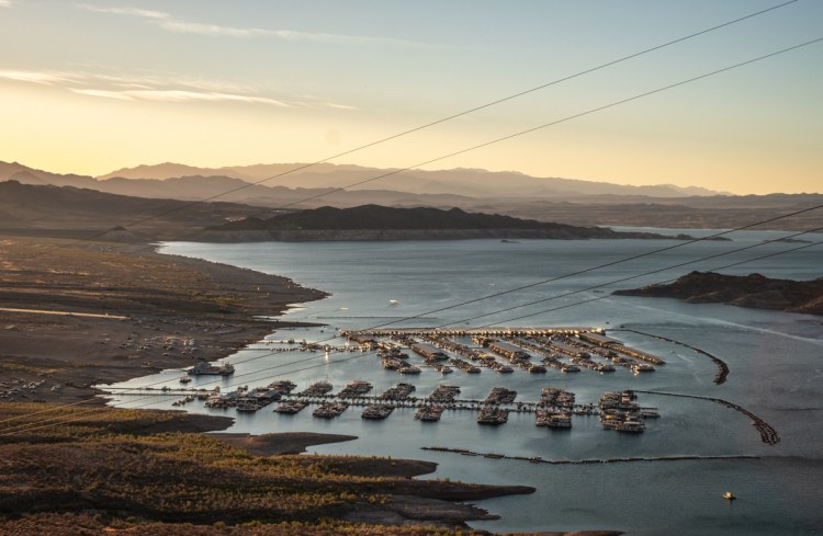 Tiny boats are lit up with the last golden light at sunset in the Hemenway Harbor of Lake Mead. The layers of mountains in the distance are also lit up with golden light.