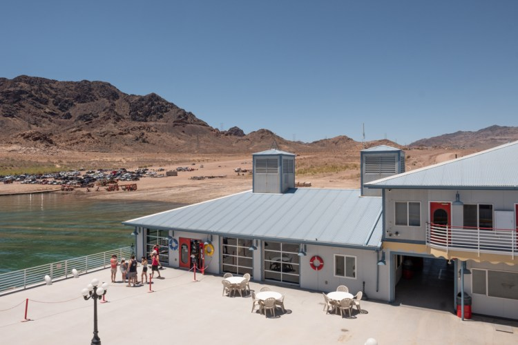 A view of the landing at Lake Mead. The mountains and the lake are in the background. A handful of people gather near the photographer on the landing. Three round, white tables with chairs are available for sitting.