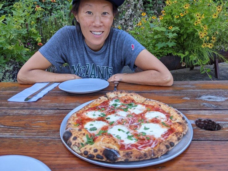 Erin McGrady is smiling at a cheese pizza from All Souls that is resting on a round, silver pizza tray on top of a wooden picnic table. There are some small yellow flowers in the background.