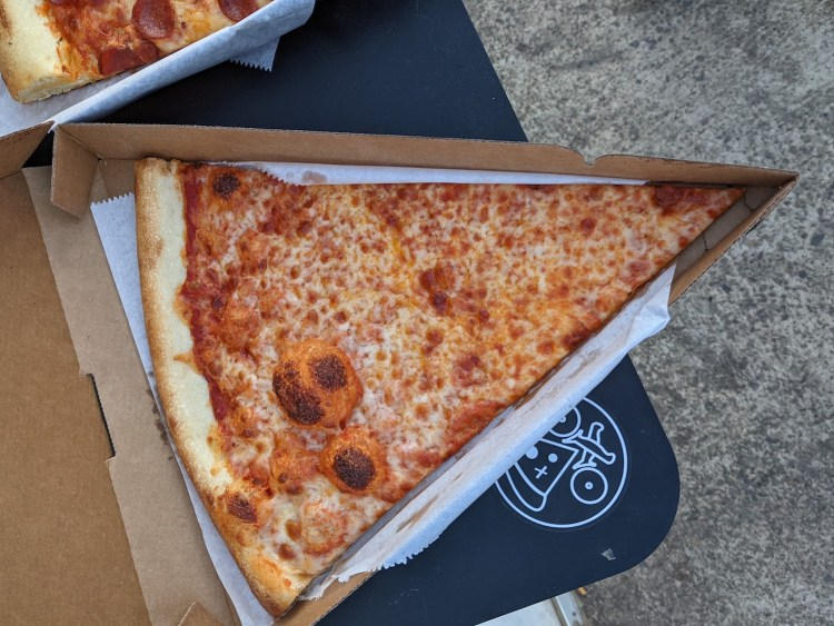 A view of a big cheese pizza slice in a cardboard box that is in the shape of a piece of pizza. The box and pizza slice are resting on a black table, outdoors, with the PIE.ZAA logo on it.