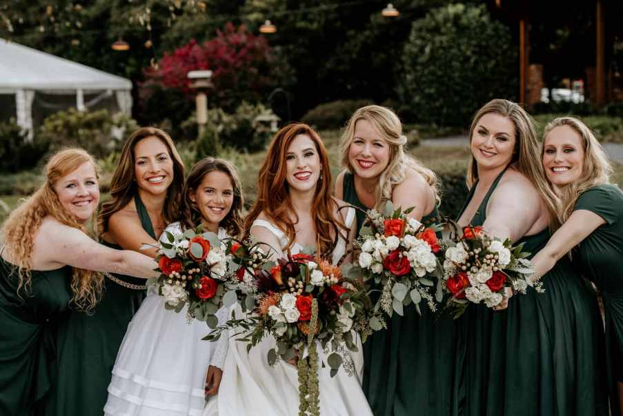 Bride and her bridesmaids showing flowers