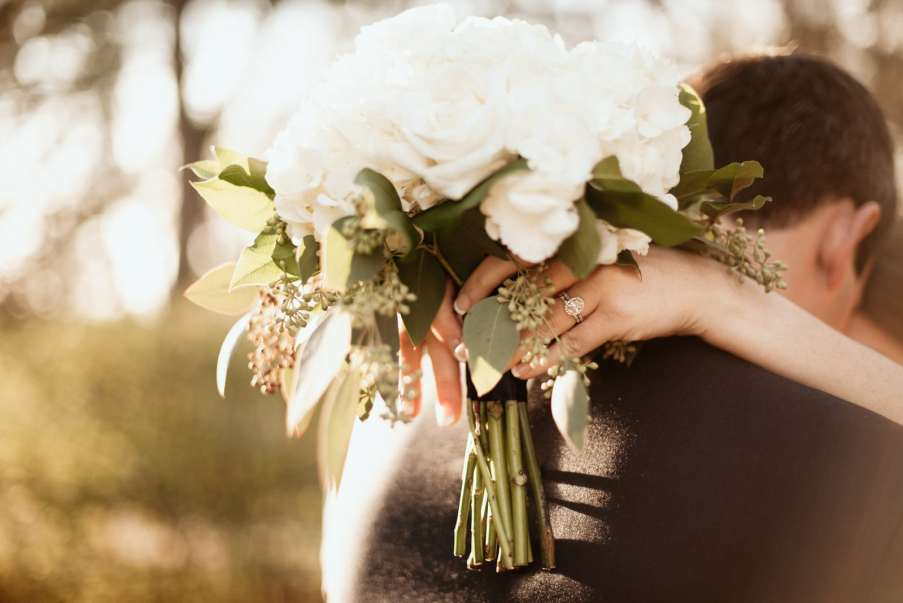 Detailed wedding ring shot with bouquet