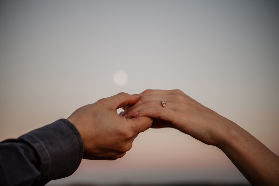 couple holding hands with engagement ring and moon
