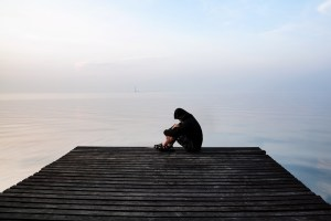 A photo of a man sitting at the end of a dock. He is experiencing symptoms of PTSD like flashbacks and panic attacks. He is going to start EMDR therapy in Castle Rock, CO | 80109 | 80108 | 80104
