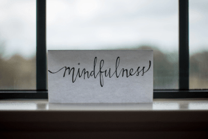 """Image of a paper reading """"mindfulness"""" propped up in front of a window. Those working with an anxiety therapist in Castle Rock, CO learn mindfulness skills to help cope with anxiety. 